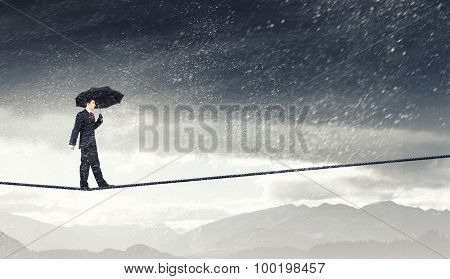 Walking on rope businessman with black umbrella