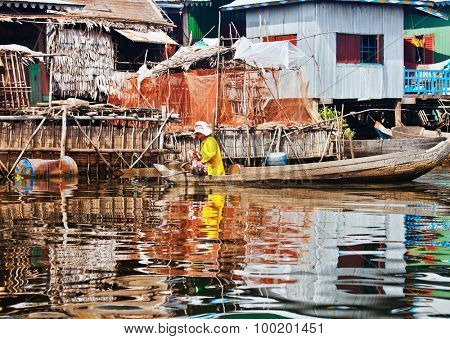 SIEM REAP, CAMBODIA - NOVEMBER 17, 2011: Cambodian woman floating in a boat on Lake Tonle Sap. Tonle Sap, the largest body of water Indochina during the rainy season, the area of 16,000 square km