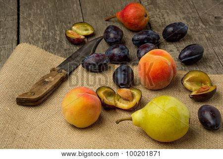 Fresh fruits on rustic wooden background: peaches  pear plums