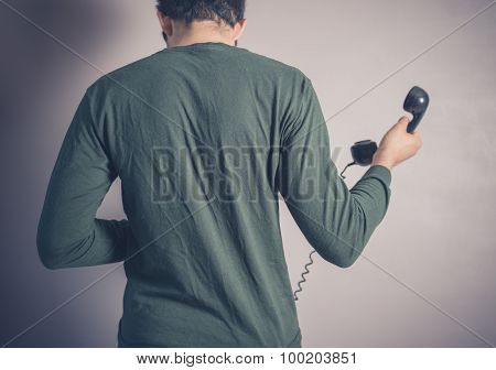 Rear View Of Man Using Rotary Phone