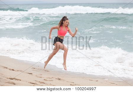 Beautiful Brunette Woman Runs On The Sand Coastline At The Morning