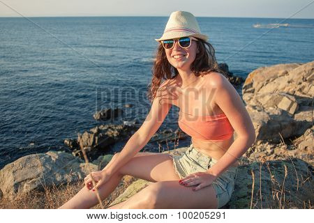 Smiling Young Woman Backpacker Sitting On Rock Near Sea