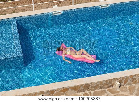 Top View Of Sexy Woman Tanning On Mattress In Pool