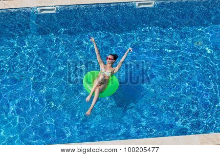 Beautiful Young Brunette Woman With Inflatable Circle In Swimming Pool
