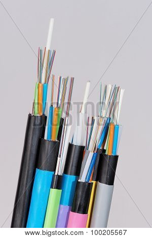 7 different fiber optic cable ends with stripped jacket layers and exposed coloured fibers