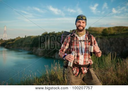 Young caucasian man with backpack resting and drinking water