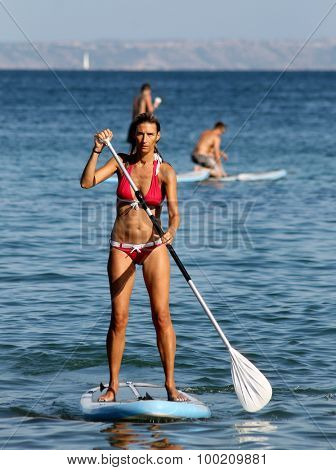 PALMA NOVA BEACH, MAJORCA, SPAIN - 25th August 2015: Palma Nova beach resort on the 25th August 2015. A young woman is paddle boarding in the foreground.