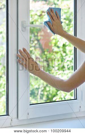 Woman washing window in room