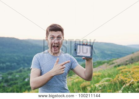 Man Hold An Ebook And Points By Finger On Book With Emotion