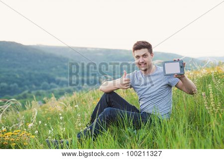 Man Sits On The Hill Hold An Ebook And Keep His Finger Up