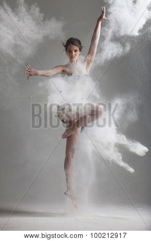 Studio portrait of woman dancing with flour