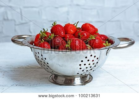 Ripe strawberries in colander on wooden table, closeup