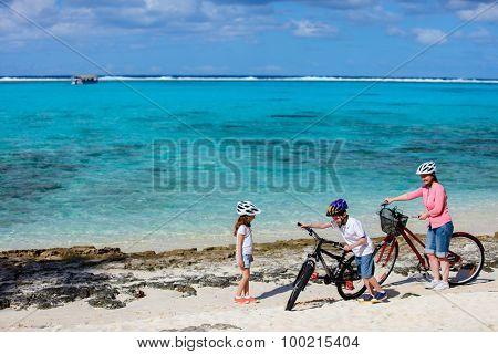 Family of mother and kids biking at tropical beach having fun together