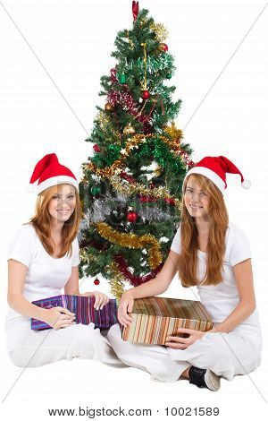 pretty sisters under christmas tree