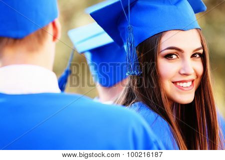 Graduated students in graduation hats and gowns, outdoors