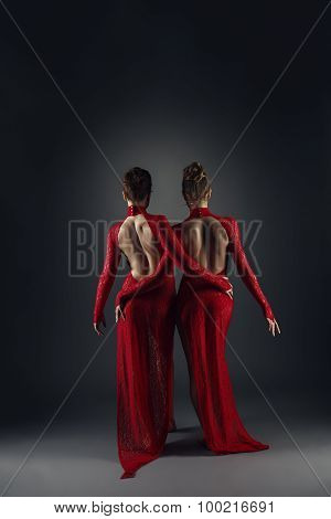 Rear view on elegant dancers in long lace dresses