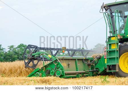ZAPORIZHZHYA, UKRAINE - July 28, 2015: Close up Photo of John Deere Combine Harvester Harvesting Wheat. Summer Harvest Concept.