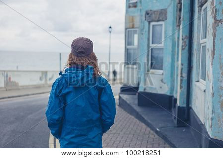 Woman Standing In Street Outside Blue House