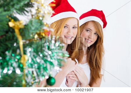 twin sisters next to christmas tree