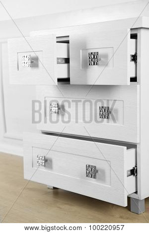White wooden chest of drawer in the interior of an room.  Open drawers
