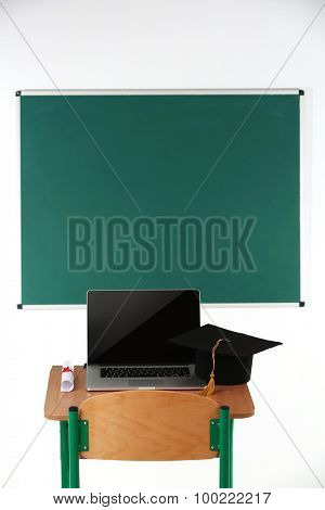 School desk with laptop, master hat and diploma in classroom