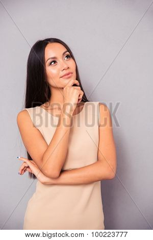 Portrait of a pensive woman in dress standing over gray background and looking up
