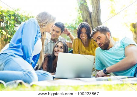 Happy friends using laptop together outdoors