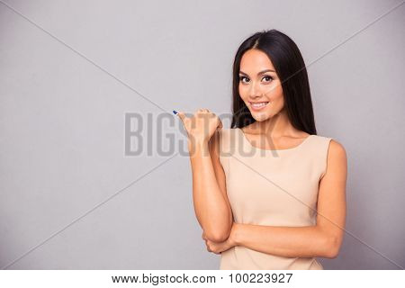 Portrait of a cheerful woman pointing finger away over gray background