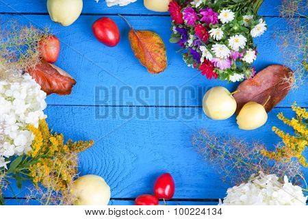 Apples, flowers, leaf litters and plums on a table