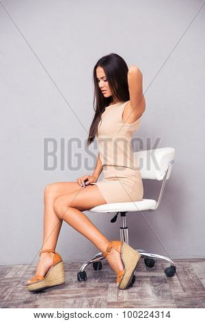 Portrait of a young woman sitting on office chair with backpain on gray background