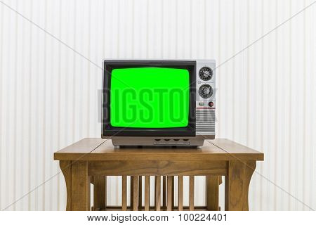 Old portable television on wood table with chroma screen