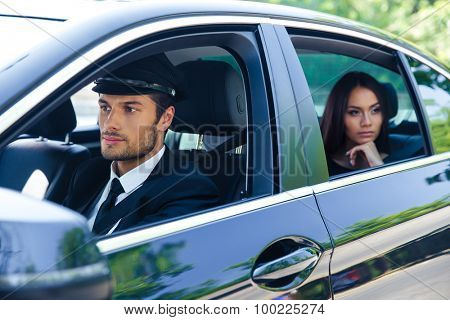 Beautiful woman riding in a car with chauffeur