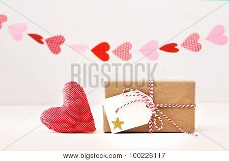 A Garland Of Hearts Above A Small Gift-wrapped Box And Textile Heart On A Off White Background