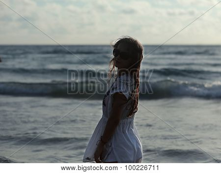 Beautiful Woman In Summer Dress Standing In Ocean In Sunset Eveing In Glasses