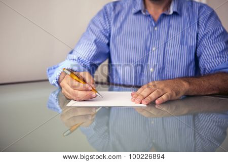 Closeup Of Man Writing On A Piece Of Paper