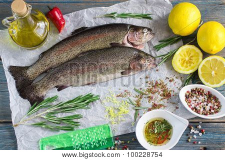 Two fresh rainbow trout with lemon, rosemary and spices