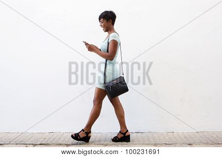 Smiling Young Woman Walking And Looking At Cell Phone