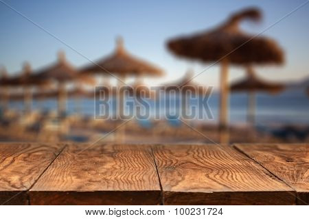 Empty wooden table with blurred beach with straw umbrellas on sunrise on background
