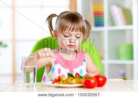 Kid girl eats fresh vegetables. Healthy eating for child