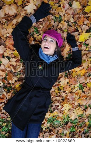 Pretty Autumn Girl Relaxing Outdoors In The Forest On The Fallen Leafs