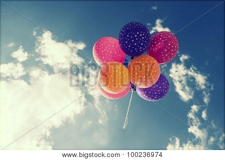 Colorful balloons on blue sky. Concept of love in summer, valentine, wedding and honeymoon. Retro styled photo