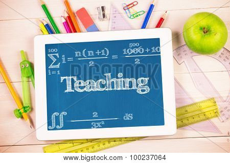 The word teaching and maths equation against students desk with tablet pc