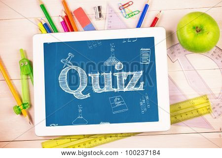 The word quiz and school doodles against students desk with tablet pc