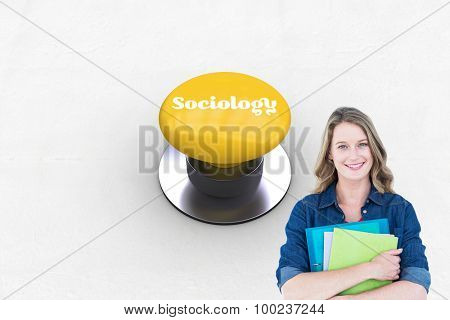 The word sociology and smiling student holding notebook and file against yellow push button