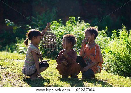Three ethnic children play with their bird in Laocai, Vietnam