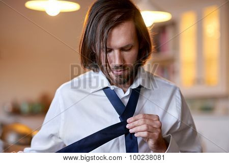 young professional man doing morning routine shirt and tie at home