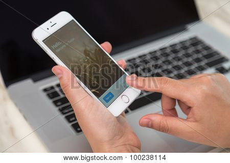 Loei, Thailand - August 12, 2015: Hand holding Iphone with mobile application for twitter on the screen