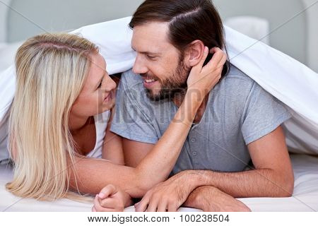 romantic young affectionate married couple intimate moment on bed under duvet at home