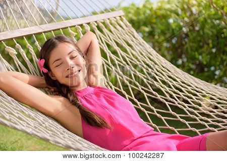 Happy relaxed young woman with hands behind head lying on hammock. Smiling mixed race Asian / Caucasian female is in casual summer dress. She is enjoying sunlight in park.