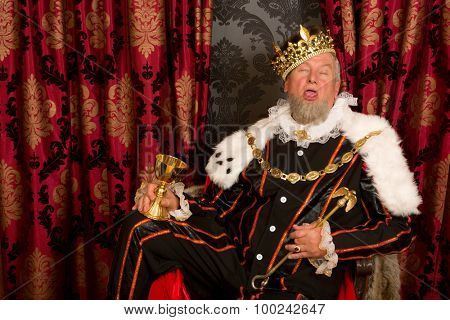 Old funny king getting drunk holding a golden goblet